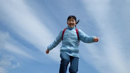 Japanese elementary school girl running and jumping  in the blue sky