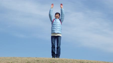 Japanese elementary school girl raising her both hands and clapping in the blue sky