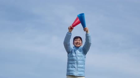gimnazjum : Japanese girl cheering with megaphone in the blue sky