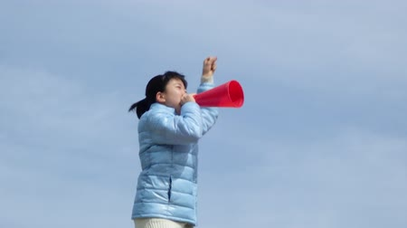 raising fist : Japanese girl cheering with megaphone in the blue sky