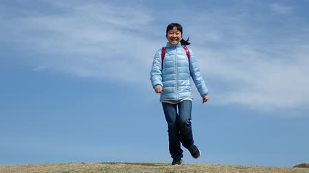 gimnazjum : Japanese elementary school girl running  in the blue sky