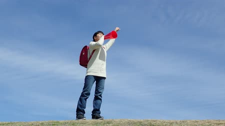 Japanese elementary school girl cheering with megaphone in the blue sky