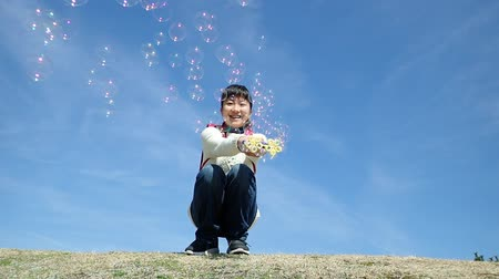 Japanese elementary school girl playing with soap bubbles in the blue sky