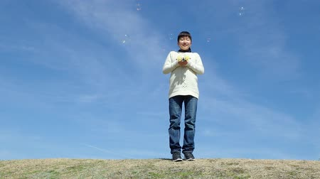 gimnazjum : Japanese girl playing with soap bubbles in the blue sky Wideo