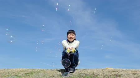 Japanese girl playing with soap bubbles in the blue sky Wideo