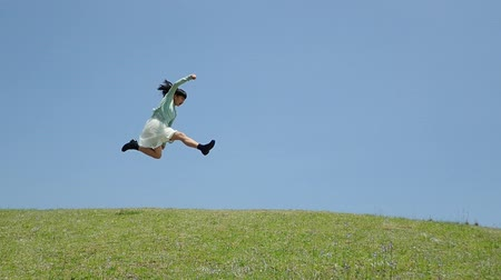 Japanese girl running and jumping in the blue sky