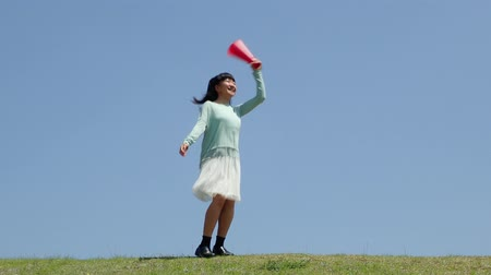 всего тела : Japanese girl cheering with megaphone in the blue sky