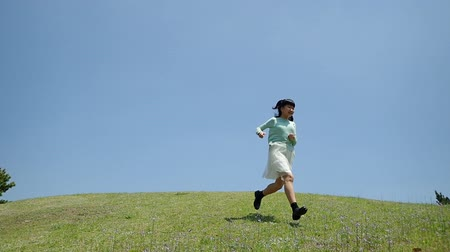 Japanese girl running down the slope in the blue sky Wideo