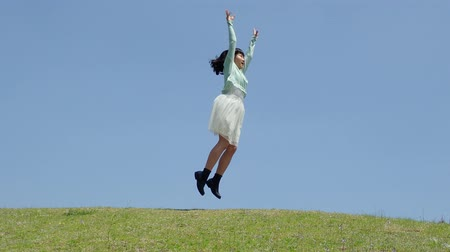 Japanese girl jumping in the blue sky