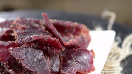 говядина : Portion of Beef Jerky (seamless loopable; with salt and pepper as close-up video)