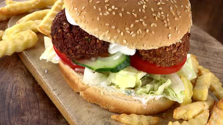 bezelye : Falafel Burger with Chips rotating on a wooden plate as seamless loopable 4K UHD footage Stok Video