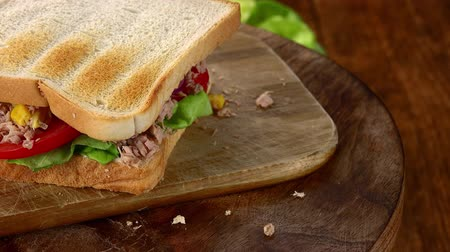 mayonaise : Tuna Sandwich rotating on a wooden plate (not loopable; 4K) Stockvideo