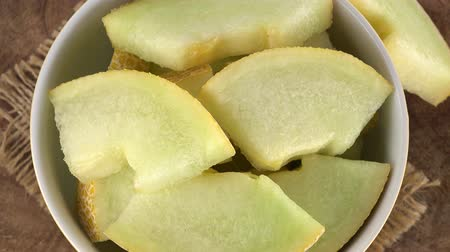 frutoso : Honeydew Melon (chopped) rotating on a wooden plate (not loopable; 4K) Vídeos