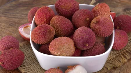 lychees : Lychees rotating on a wooden plate as seamless loopable 4K UHD footage