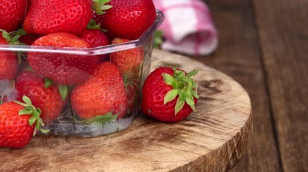 fresh produce : Strawberries rotating on a wooden plate as seamless loopable 4K UHD footage