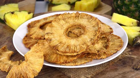 konzervovaný : Portion of Dried Pineapple rings rotating on a wooden plate (not loopale; 4K)