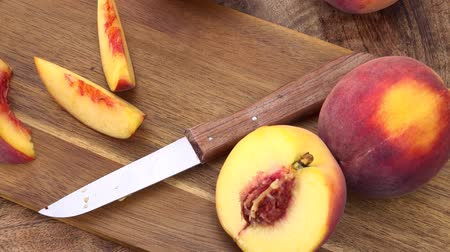 őszibarack : Peaches rotating on a wooden plate as seamless loopable 4K UHD footage Stock mozgókép