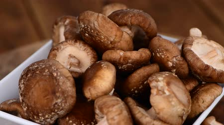 shiitake : Shiitake mushrooms rotating on a wooden plate as seamless loopable 4K UHD footage