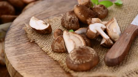 shiitake : Raw Shiitake mushrooms on a rotating wooden plate (seamless loopable; 4K)