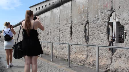 ss : girls taking pictures of berlin wall, germany