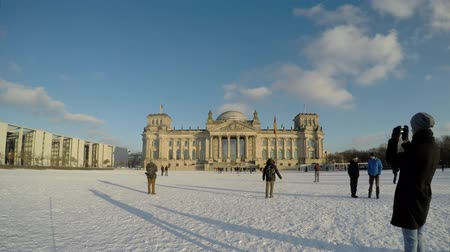 chancellery : Reichstag building German Bundestag time lapse in winter on a snowy day. Many people tourist sight seeing in Berlin. Berlin time lapse footage - Berlin, Germany video.
