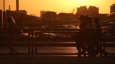 warszawa : Silhouette of people walking, on busy bridge at Warschauer Strasse in Berlin at sunset. Wideo