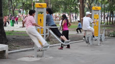 vietnamec : Saigon, Vietnam - june 7, 2016: Woman exercising on fitness equipment outdoor in park in Saigon, Vietnam.