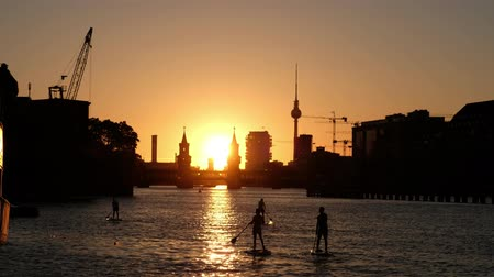 oberbaum : Group of paddle boards  stand up paddle on river spree in Berlin - Oberbaum Bridge, Germany Tower and sunset sky background Stock Footage