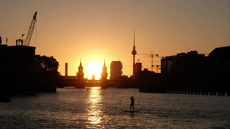 oberbaum : One person standing on paddle board on river Spree with sunset sky, Oberbaum Bridge and Tv tower background