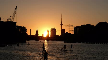 berlin skyline : Sunset sky Berlin panorama - river Spree, Oberbaum Bridge, Tv Tower and stand up paddle board people Stock Footage