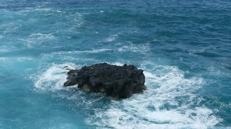 black rock in ocean waves
