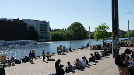 pitka : Young people sitting at the river next to Berlin Wall on a sunny summer day