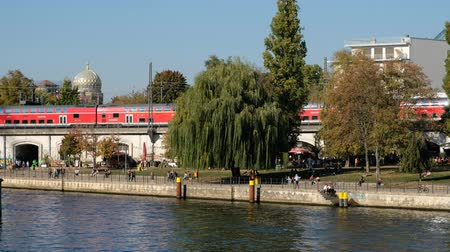dava : People in public park (Monbijoupark)  Riverside in Berlin Mitte with trains passing on a sunny summer day