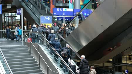 old times : traveling people with luggage on escalator inside crowded train station in Berlin, Germany