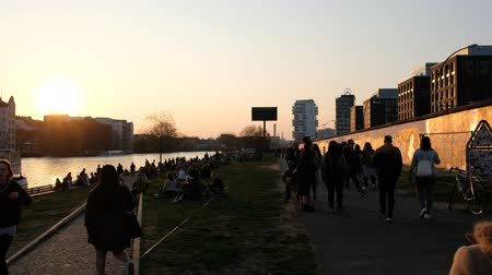 rampart : People at riverside next to the Berlin Wall during sunset in Berlin, Germany