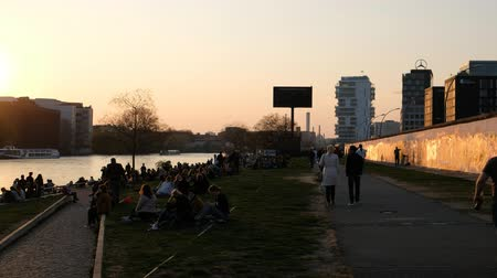 berliner mauer : Many young people at crowded riverside next to Berlin Wall  East Side Gallery in Berlin, Germany