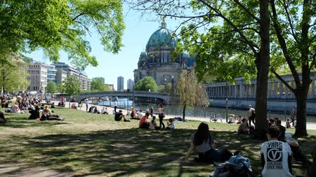 ileri : People enjoying summer in the city, outdoor in park (Monbijoupark) Walking on sidewalk next to river Spree in Berlin, Mitte