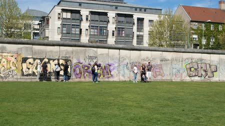 граффити : People visiting the Berlin Wall Memorial, one of Berlins tourist attractions and most famous landmarks