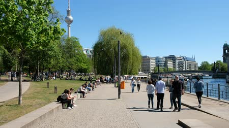 pitka : People enjoying summer in the city, outdoor in park (Monbijoupark) Walking on sidewalk next to river Spree in Berlin, Mitte