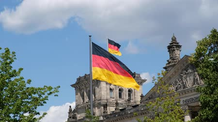 bundestag : German flag, flags of germany waving on Government building (Reichstag) in Berlin Germany