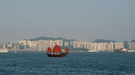 Sailing boat on Victoria Harbor and skyline view of Hong Kong Island at dayt Stock Footage