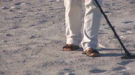 alkol : Feet of man with metal detector
