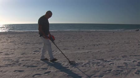 alkol : Man with metal detector on a beach