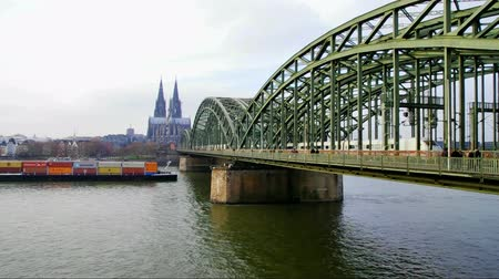 kolínská voda : container ship passing the Hohenzollern bridge in cologne, germany. In the background the famous cathedral of cologne