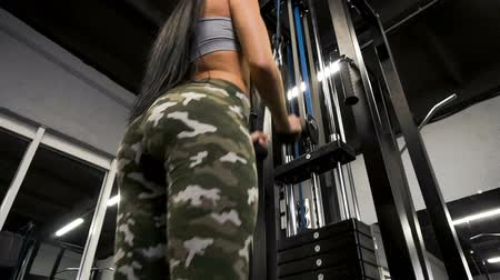 exercisemachine : Young sporty girl working out on pull-down machine in gym. Stock Footage