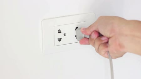 unplug : Close Up Of A Hand Plugging In A Power Cord And Then Unplugging It In A Typical Electrical Outlet.