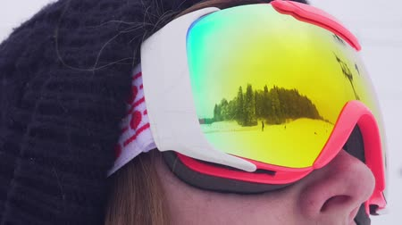 sporty zimowe : Mountains and people skiing and snowboarding reflected in a ski mask illuminated solar flare