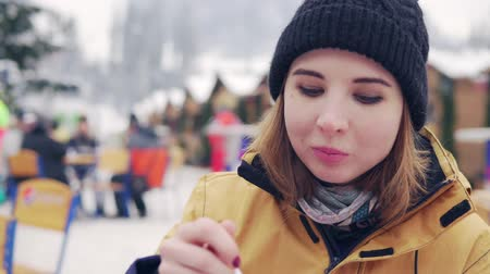 cop : Beautiful blonde eats pilav against background of winter market Dostupné videozáznamy
