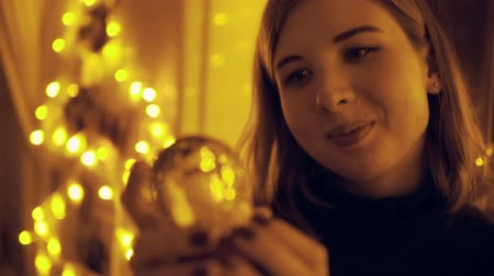 image house : Portrait of a young woman with fairy lights in the house shaking the snow globe