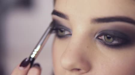 eyeshade : Make-up artist applying eye shadow makeup to models eye. Close up view. Smoky eyes. Right view Stock Footage